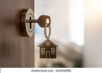 Open door to a new home with key and home shaped keychain. Mortgage, investment, real estate, property and new home concept - Shutterstock ID 1654410982