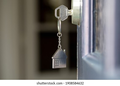 Open door to a new home with key and home shaped keychain. Mortgage, investment, real estate, property and new home concept business