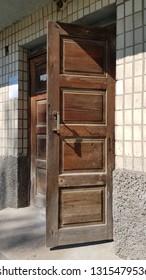 Open door with old dirty wooden panels and retro door handle. Rustic wooden door. Grunge entrance to old building with open shabby door. Weathered wood texture