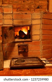open door of the oven - a fireplace in the rural house, a poker and fire in the furnace