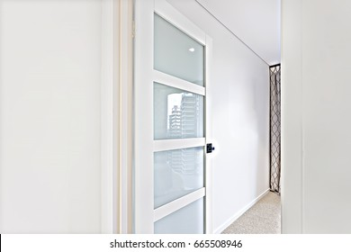 Open door to a room close up with white walls  in a modern house or hotel, the door is made of glass and wood which gives a reflection of a city building