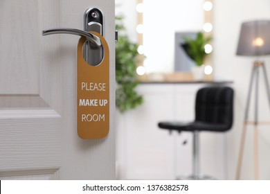 Open door with sign PLEASE MAKE UP ROOM on handle at hotel, space for text