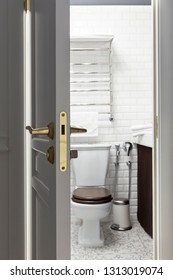 An open door to a toilet room with closeup at lock/handler and toilet as a background