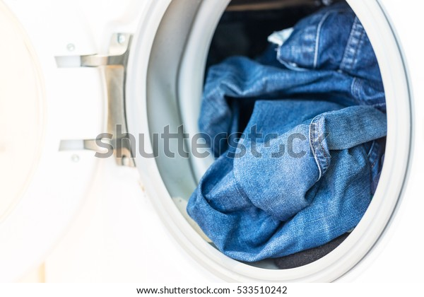 Open door in washing machine with jeans inside close up