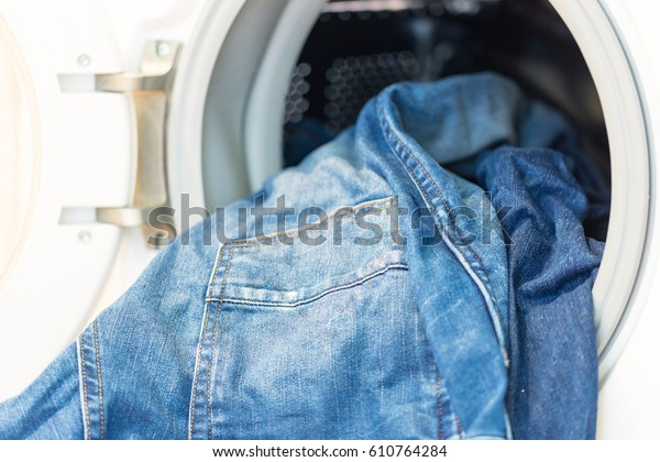Open door in washing machine with jeans inside ready for wash close up