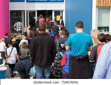 It is an open doors day in a school. We see a big queue of adults and children near to the school. Children and their parents – all together welcome to school!