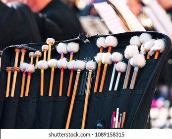 Open drummer bag with drumsticks; mallets & brushes and other musician equipment near the timpani. Performance of symphony orchestra outdoors.