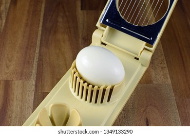 Open egg slicer with boiled egg ready for slicing. Space for text.
