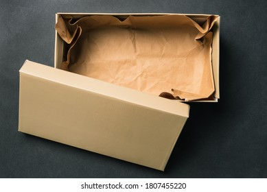 Open empty box with a lid, isolated on a black background. Cardboard box for shoes or gift. Top view, flat layout