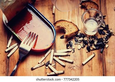 Open empty canned fish,fork,shots, seeds husk, bitten bread and cigarette butt