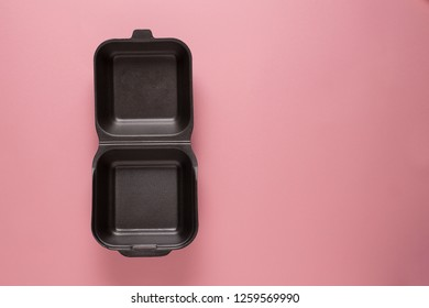 Open empty foam delivery box, pink background. Take away food packaging