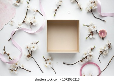 open empty gift box on white table. Colorful Gift box with ribbon bow present on holiday with cherry and apricot flowers