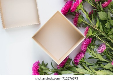 open empty gift box on white table asters. Colorful Gift box with flowers. present on holiday