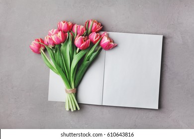 Open empty notebook and bouquet of pink tulip flowers on gray stone table top view in flat lay style. Woman working desk.