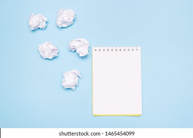 Open empty notebook and crumpled paper balls on blue paper background. Creation process, idea or creative attempts concept. Copy space.