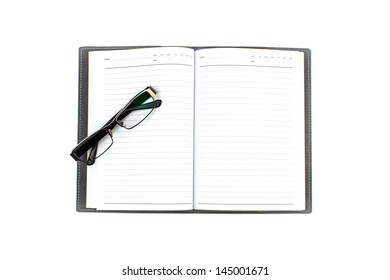 Open empty notebook with glasses and lined pages
