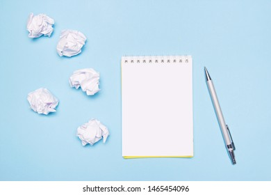 Open empty notebook, pen and crumpled paper balls on blue paper background. Creation process, idea or creative attempts concept. Copy space.