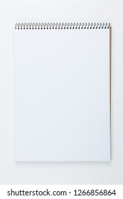 open empty notebook vertical on the white table top view, spiral notepad with blank page. flat lay of office concept