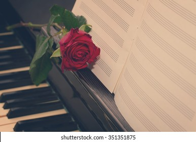 open empty notes paper with red rose   on vintage piano, retro toned