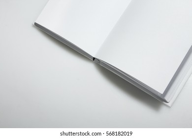 Open empty white book on a gray background.