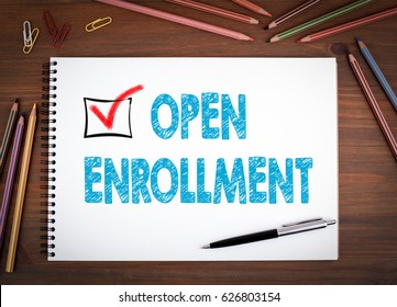 Open Enrollment. Notebooks, pen and colored pencils on a wooden table.