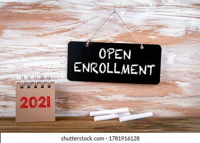 OPEN ENROLLMENT. Small chalk board and white chalk on a wooden background