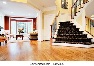 Open entryway with wood floor and staircase, with view of living room. Horizontal format.