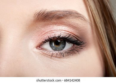 Open eye of a girl with makeup, background.
