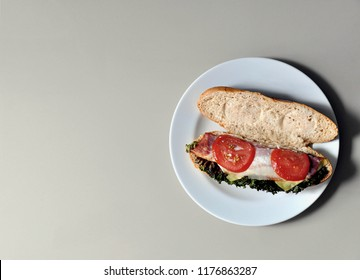 Open face grilled BLT baguette sandwich on round white plate shot from above or top view showing the component or ingredients. Copy space on the left ready for text.