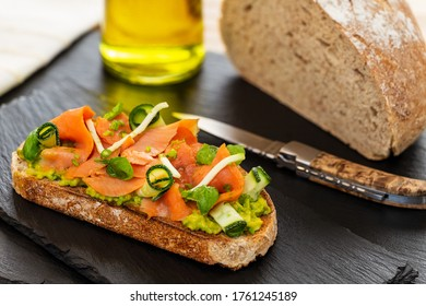 Open faced sandwich or French tartine with smoked salmon, avocado, zucchini rolls, basil, chives and apple on a toasted slice of sourdough bread. With knife, bread loaf and olive oil on slates.