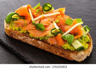 Open faced sandwich or French tartine with smoked salmon, avocado, zucchini rolls, basil and minced chives and apple on a toasted slice of sourdough bread. Displayed on slates.
