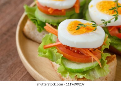 Open faced sandwich with toast lettuce tomato carrot cucumber and boil egg on wooden plate in close up view. Delicious breakfast for family served on wood table. Homemade and healthy food concept.