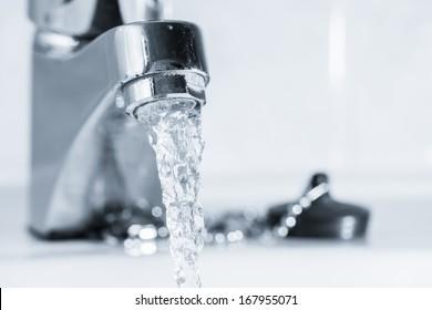 Offener Wasserhahn im Badezimmer, Wasser läuft, schwarz-weißes Bild, Horizontformat