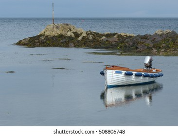 Open fibre glass boat, Carvel Built style, with outboard moored in a little cove at Donaghadee, Co Down. This spot located in the Irish Sea with the Copeland Islands a mile away is great for fishing.