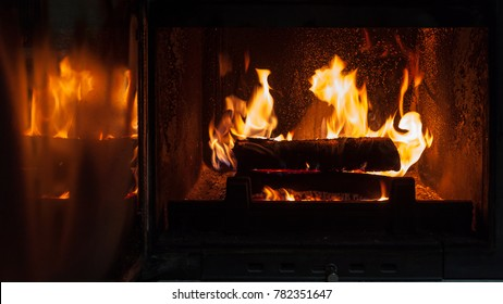 open fireplace with wood burning and reflection on the glass