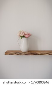 Open floating wooden shelf with a big ceramic jug of pink pastel flowers on a white wallpaper wall in a modern design living room
