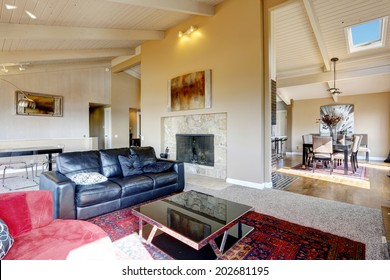 Open floor plan in big luxury house. View of spacious living room with fireplace, black leather couch and coffee table
