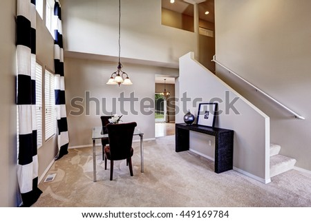 Open Floor Plan Dining Room With Carpet And Glass Table