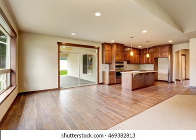 Open floor plan. Empty living room with carpet floor. Connected to kitchen area. View of exit to backyard. Northwest, USA