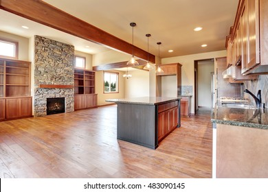 Open floor plan. Kitchen room interior with wooden cabinets, island and granite counter top. Connected to living room with stone fireplace. Northwest, USA