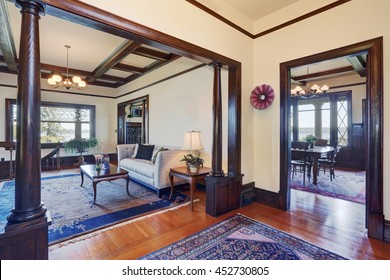 Open floor plan of living room and dining room in old style house. White walls with brown trim and hardwood floor.