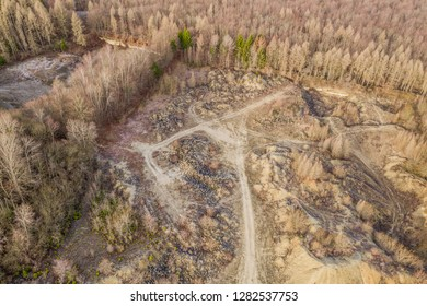 Open former limestone quarry in the Elm mountains with an ugly slag heap and useless overburden, deciduous forest in the surrounding area.