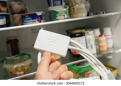 Open fridge door with male hand holding new Wifi dongle for modern refrigerators with new fridge in background - control with app and smartphone