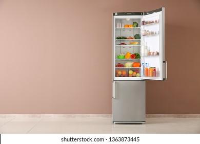 Open fridge full of food near color wall