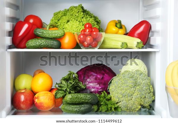 Nevera abierta llena de verduras y frutas