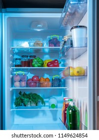 Open fridge with healthy fresh food inside including assorted fruit and vegetables and bottles of juice in the door