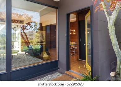 Open front door with large window next to it.