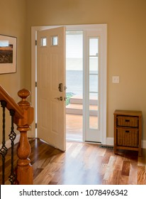 Open front door leading onto wood steps with lobby or hall with hardwood flooring