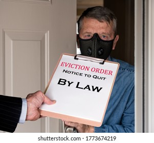 Open front door with man in suit handing an eviction notice to a defaulting renter with face mask during coronavirus epidemic