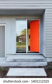 Open front door, a soothing orange door greets the visitor.